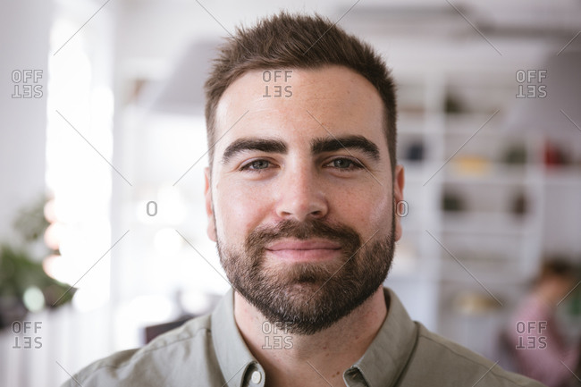 Portrait close up of a happy Caucasian businessman working in a modern office, looking straight at camera and smiling