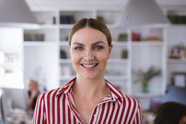 Portrait of a happy Caucasian businesswoman working in a modern office, looking at camera and smiling, with her colleagues working in the background