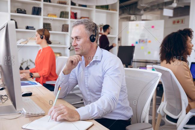 A Caucasian businessman working in a modern office, sitting at a desk, wearing headset and talking on the phone, with his business colleagues working in the background