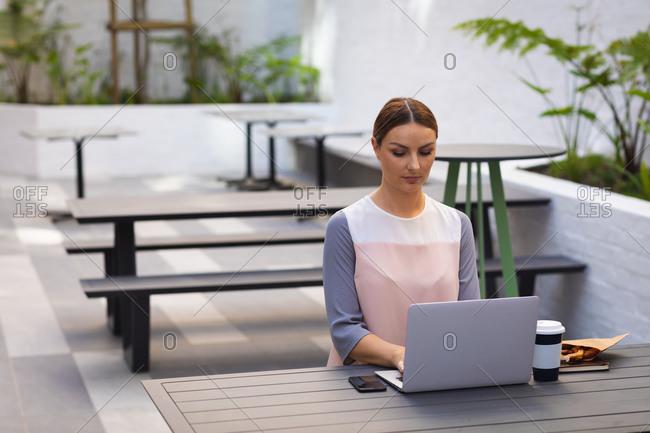 A Caucasian businesswoman on the go on a sunny day, sitting at a table and working on her laptop, with a takeaway coffee on a table