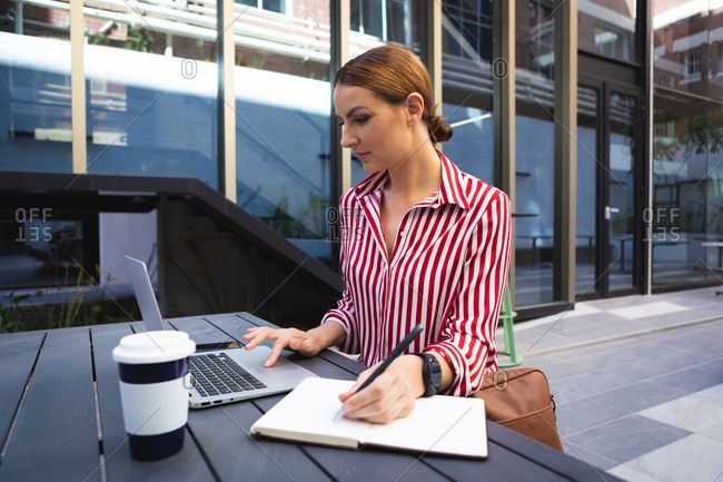 A Caucasian businesswoman on the go on a sunny day, sitting at a table, using her laptop and taking notes, with a takeaway coffee on a table