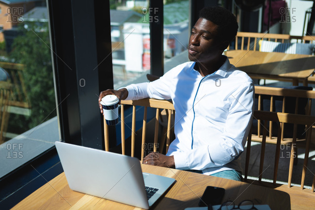 An African American businessman sitting at a table inside a cafe, working on his laptop and thinking, holding a cup of coffee