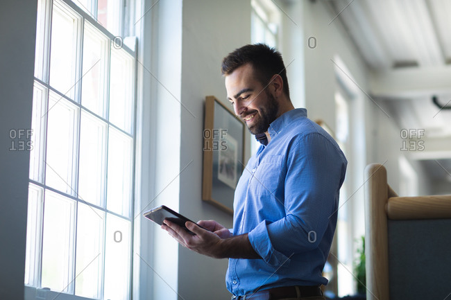A Caucasian businessman with short hair, wearing a blue shirt, working in a modern office, standing by the window and using his tablet