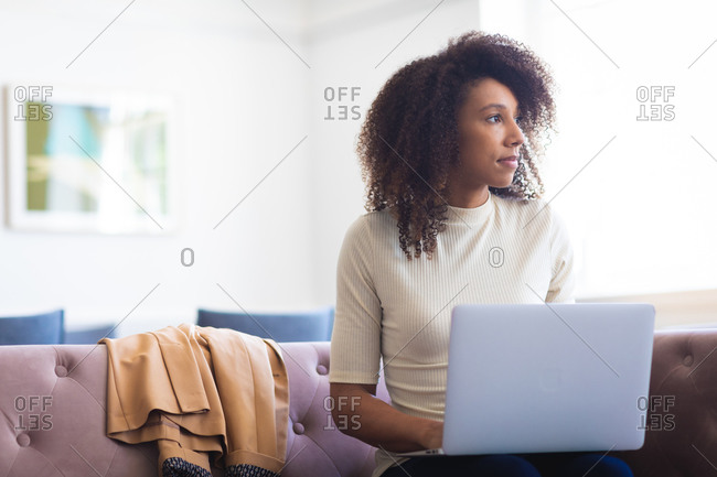 A mixed race businesswoman with curly hair, working in a modern office, sitting on a sofa and working on her laptop