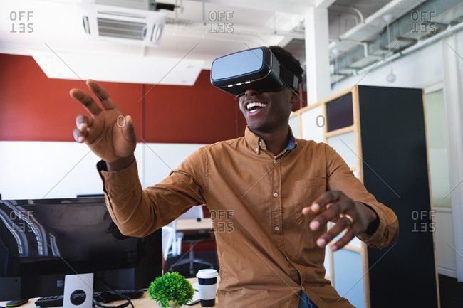 An African American man, working in a modern office, sitting on a table and smiling, wearing VR headset and touching virtual interactive screen