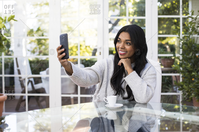 Happy young woman taking selfie through smart phone at table in coffee shop
