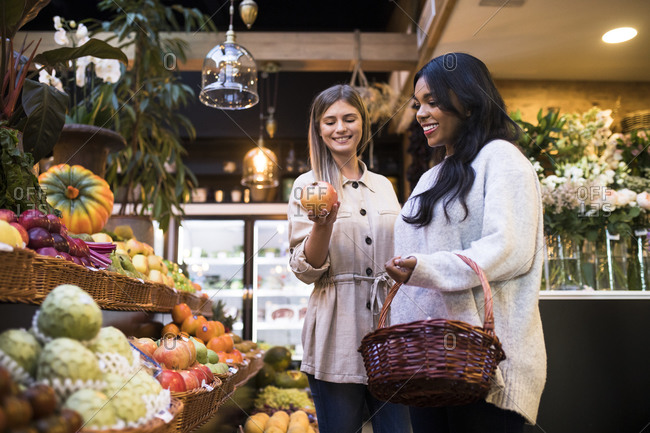 Happy multi-ethnic friends buying fruits in grocery store