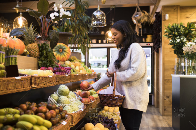 Young woman carrying wicker basket while buying fruits in grocery store