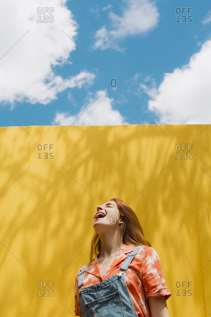 Cheerful young woman with mouth open standing over yellow wall against cloudy sky