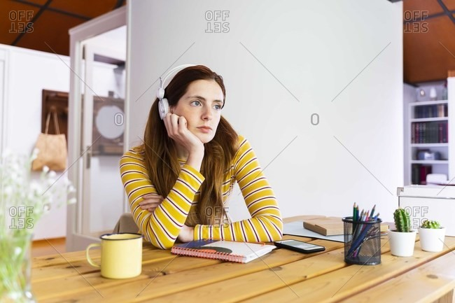Thoughtful young woman wearing headphones while sitting at desk