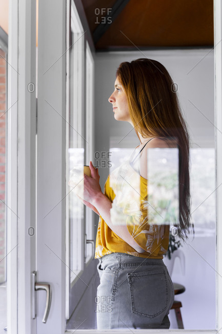 Thoughtful woman holding mug while looking through window at home seen through glass