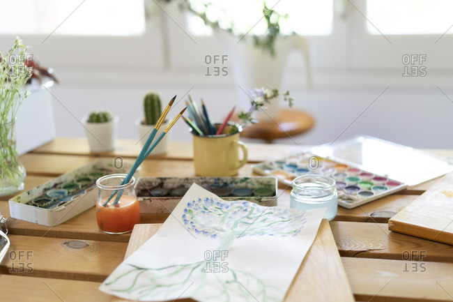 Watercolor paints with drawing and paintbrushes on wooden table home