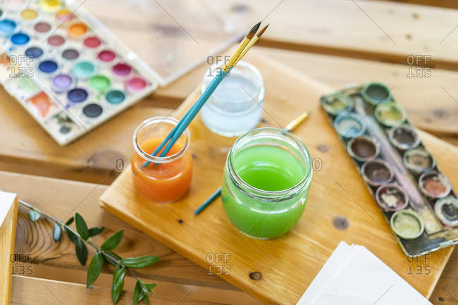 Watercolor paints with water and paintbrushes on wooden table home