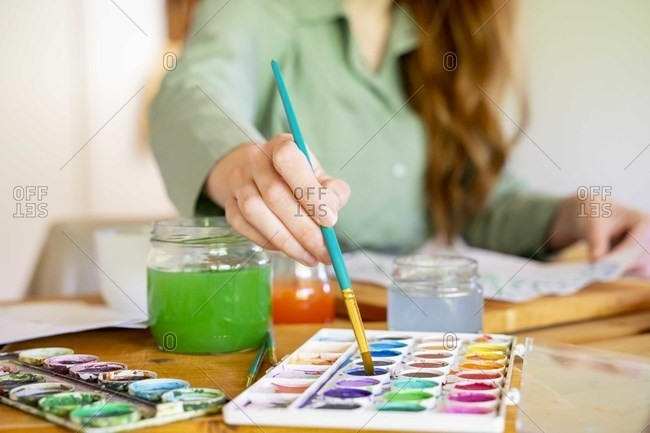 Young woman dipping paintbrush in watercolor on table at home