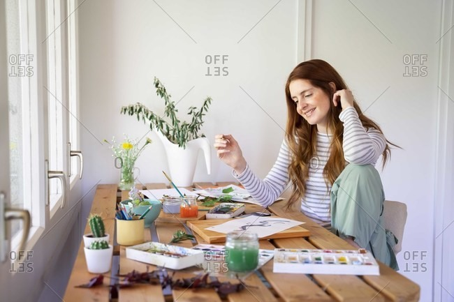 Happy young woman painting with watercolor paints on table at home