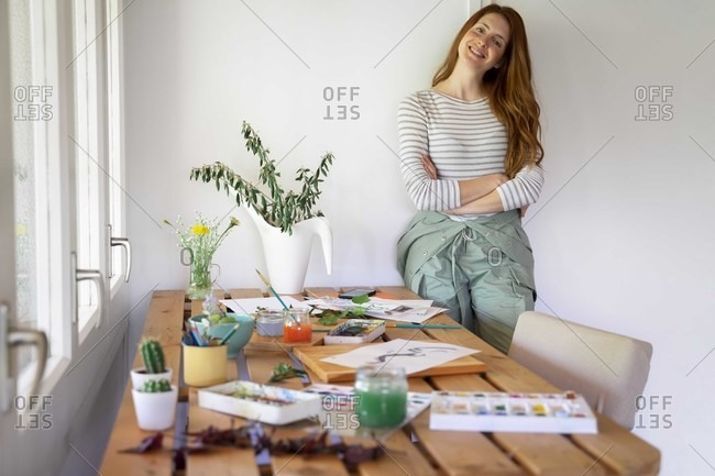 Happy young woman standing by table with watercolor paints at home