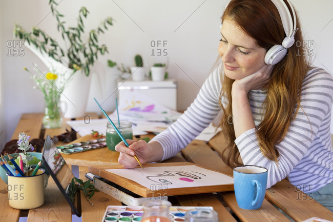 Young woman listening music though headphones while painting at home