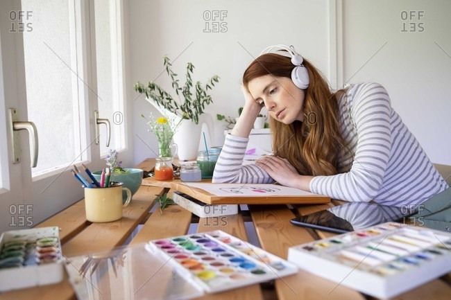 Thoughtful woman listening music though headphones while painting at home