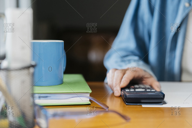 Senior man holding calculator while working at table