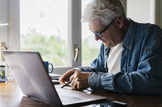 Senior man repairing laptop at home