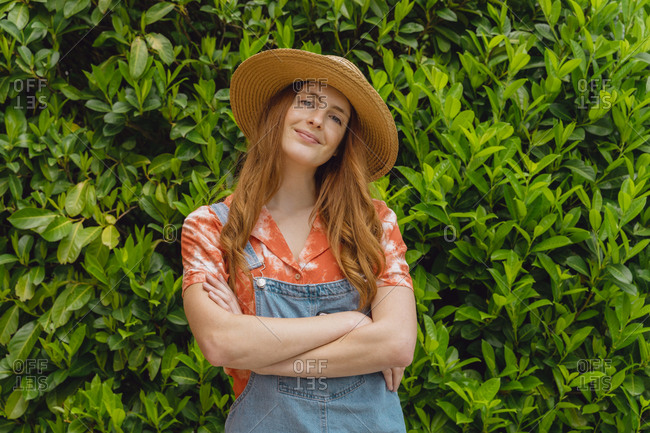 Smiling beautiful young redhead woman standing with arms crossed against green plants at back yard
