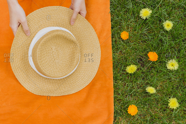 Hands of woman holding hat on picnic blanket by flowers at back yard