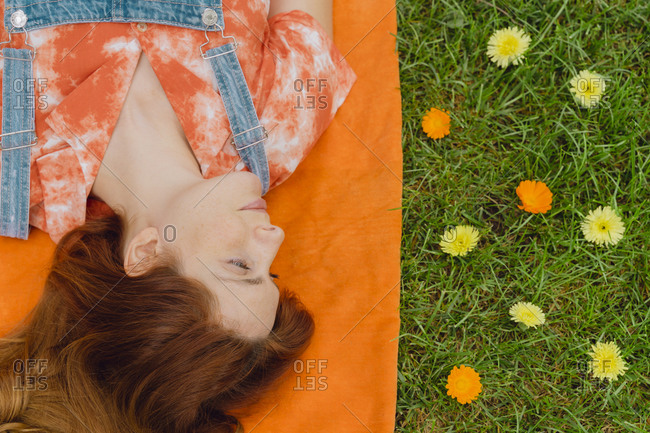 Beautiful redhead woman lying on picnic blanket by flowers at back yard
