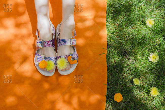 Flowers on feet of woman relaxing at back yard