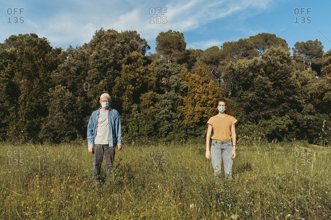 Woman and senior man with masks standing on meadow- safety distance