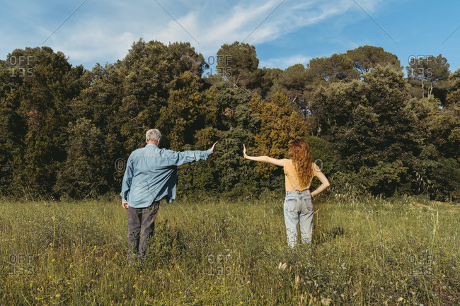Rear view of woman and senior man with masks standing on meadow- safety distance