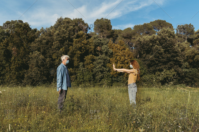 Woman and senior man with masks standing on meadow- holding safety distance