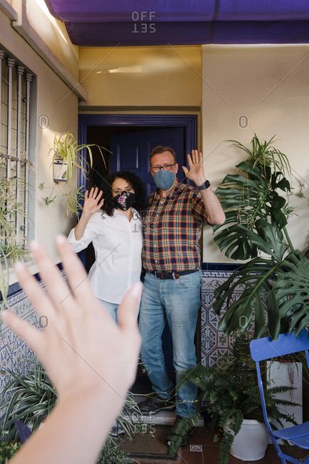 Couple wearing masks waving hands to neighbor while standing at entrance of house