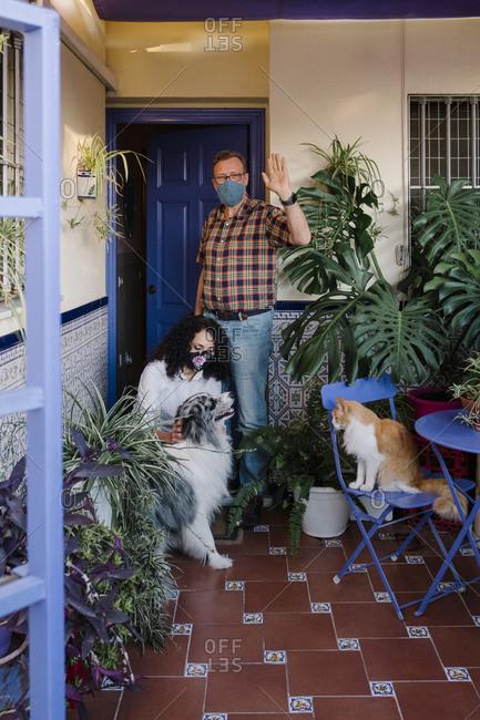 Man wearing mask waving hand while woman petting dog in yard