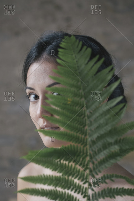 Beautiful young woman hiding behind fern leaves