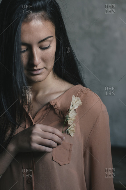 Beautiful young woman inserting flowers in pocket