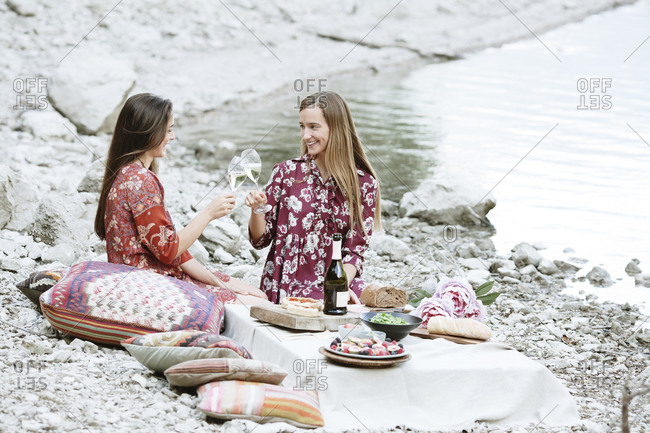 Female friends toasting wineglasses while sitting at lakeshore