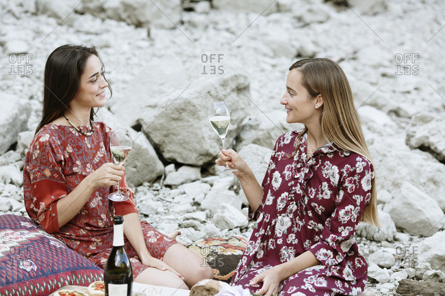 Female friends holding wineglasses talking while sitting against rocks