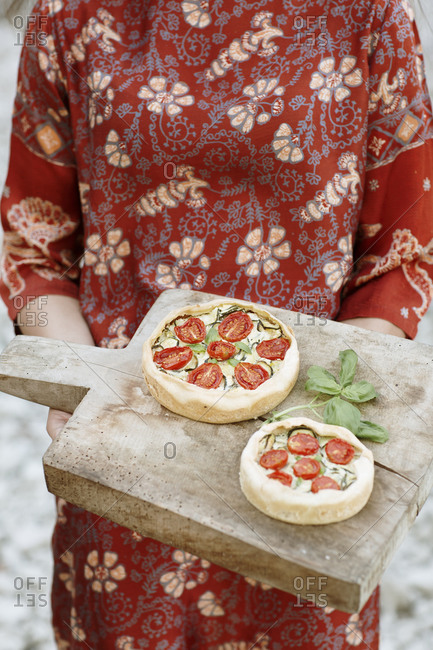 Close-up of young woman holding savory pie on serving board while standing outdoors