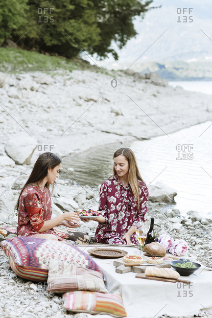 Woman offering fruit salad to female friend while enjoying picnic at lakeshore