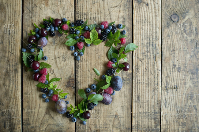 Heart shape made of fresh berries- plums and cherries on wood