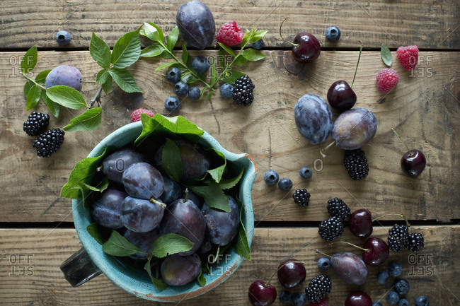 Jug and fresh berries- plums and cherries on wooden surface