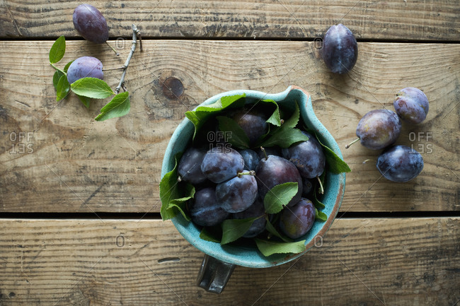 Jug of fresh plums standing on wooden surface