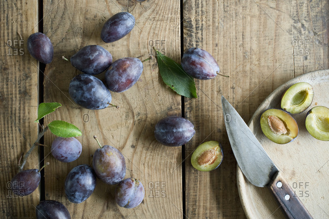 Kitchen knife and fresh plums on wooden surface