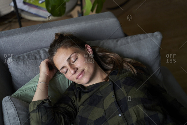 Smiling mid adult woman with eyes closed relaxing on sofa in living room