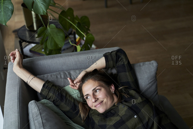 Smiling woman stretching hands looking away while lying on sofa at home