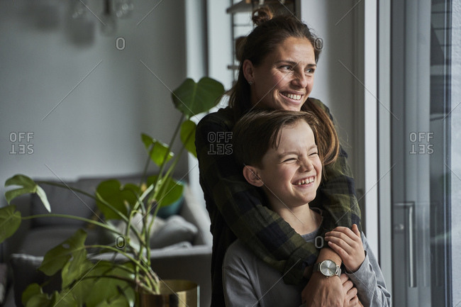 Happy mother and son looking through window while standing at home