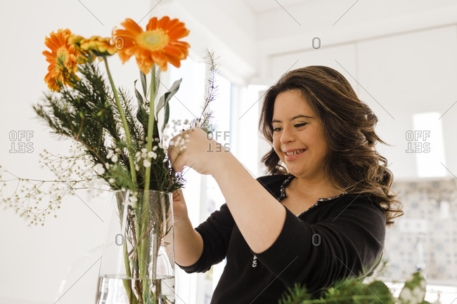 Happy young woman with down syndrome arranging flowers in vase at home