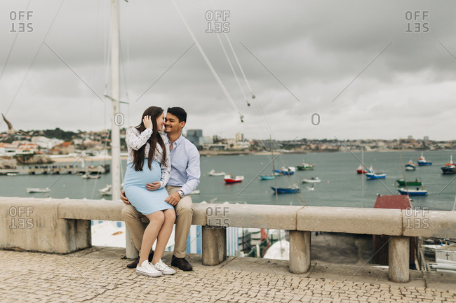 Romantic expectant couple sitting on retaining wall at harbor- Cascais- Portugal