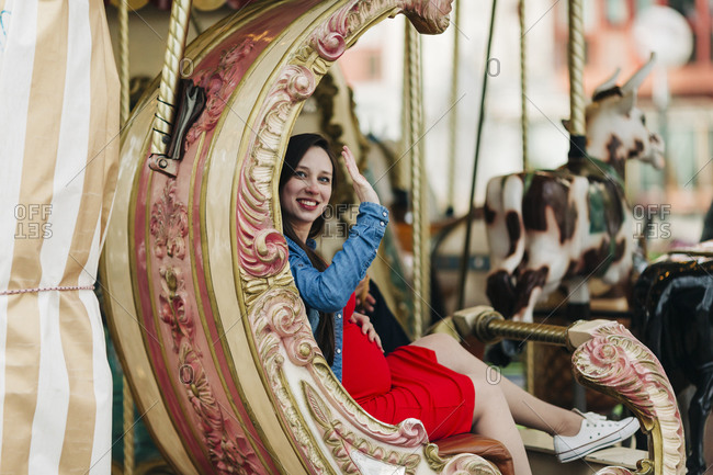 Happy pregnant woman waving while sitting on carousel at amusement park- Cascais- Portugal