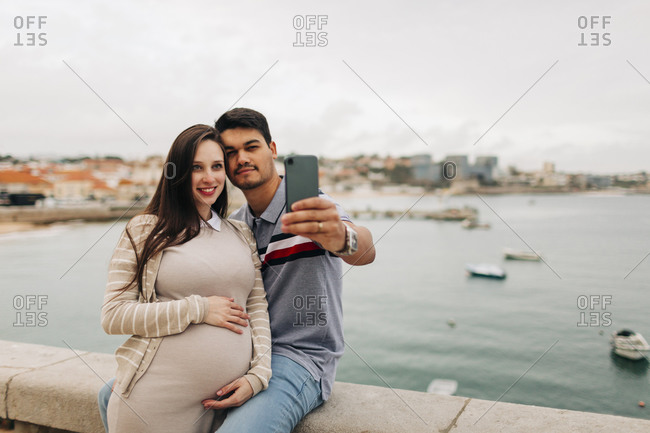 Expectant couple taking selfie through smart phone at harbor- Cascais- Portugal